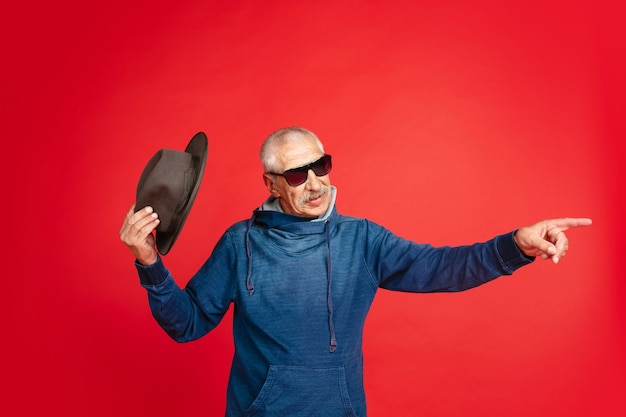 Senior man in stylish eyewear and hat isolated on red