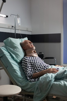 Senior man suffering after serious accident laying in hospital bed, wearing neck brace