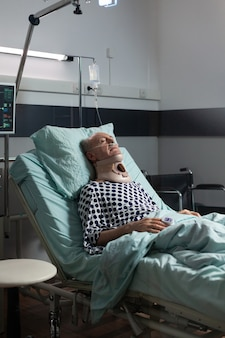 Senior man suffering after serious accident laying in hospital bed