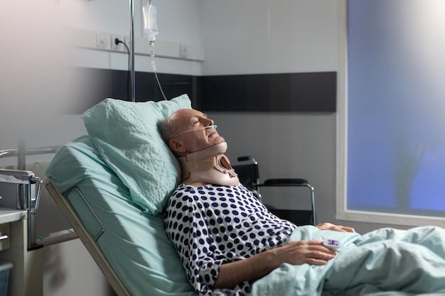 Старший мужчина страдает после серьезной аварии, лежа на больничной койке