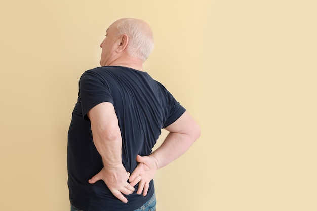 Senior man suffering from back pain on light background