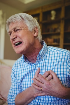 Senior man suffering from chest pain in living room