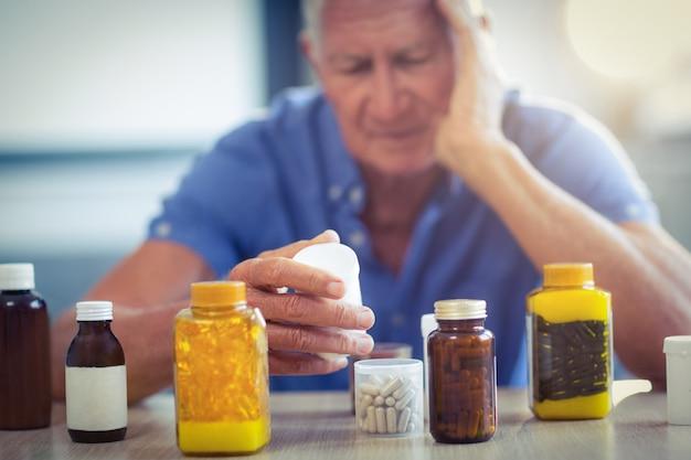 Senior man suffering from headache with prescription bottle