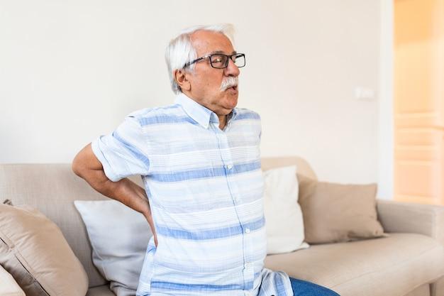 背中の痛みに苦しんでいる年配の男性