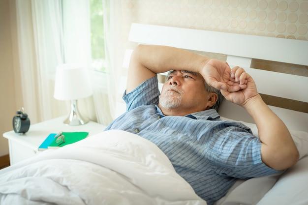 ベッドで苦しんでいる年配の男性は不眠症から眠ることができません、年配の男性、老人は朝ベッドから目覚めたくない-高齢者の不眠症の問題の概念