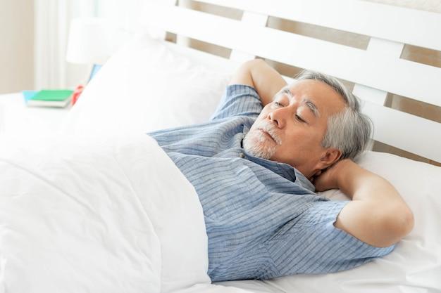 ベッドで苦しんでいる年配の男性は不眠症から眠ることができません、年配の男性、朝ベッドで寝ている老人-高齢者の不眠症の問題の概念