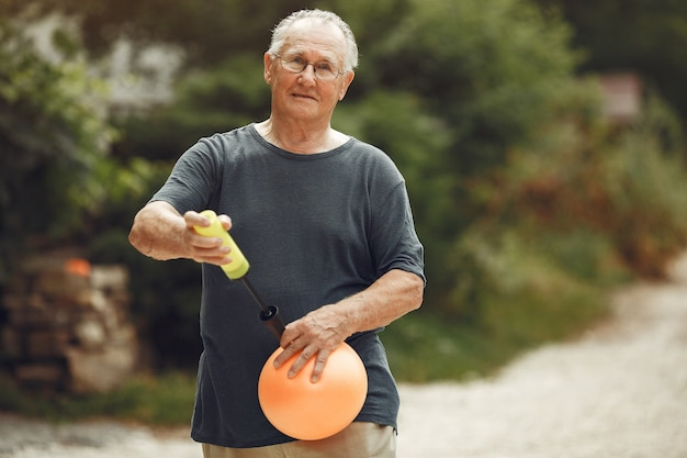 Uomo maggiore al parco estivo. nonno che usa una pompa a palloncino.