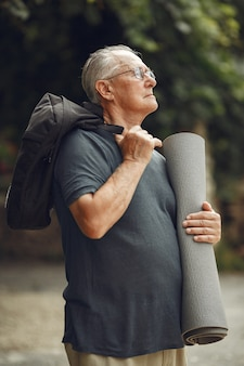 Senior man at summer park. grangfather with a mat.