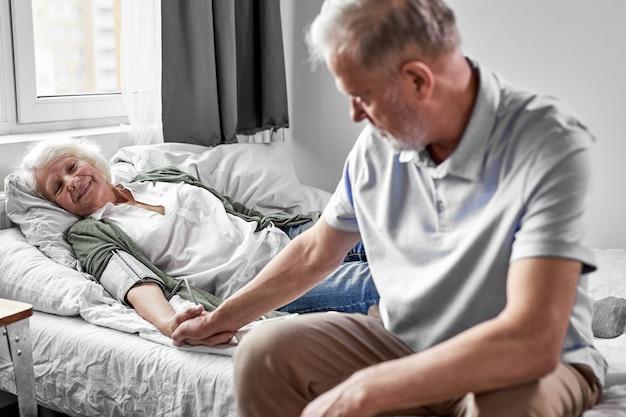 彼女の手を握って、病院で彼女の病気の妻をサポートする年配の男性。女性は気分が悪い。健康と医学の概念