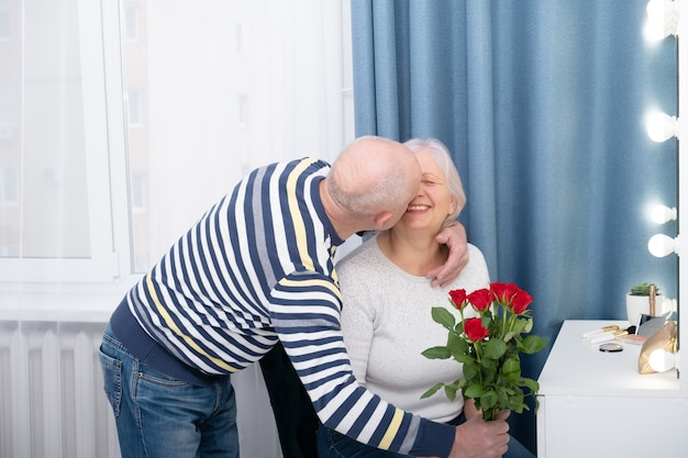 Старший мужчина удивляет жену с розой, целуя ее. отношения, стареют вместе, концепция любви.