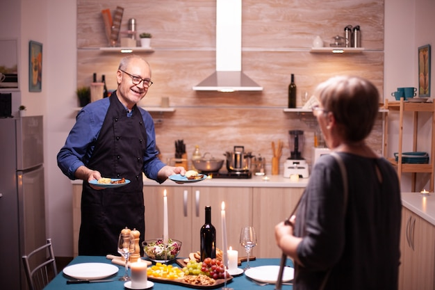 Senior man surprising wife with romantic dinner and tasty food. elderly couple talking, sitting at the table in kitchen, enjoying the meal, celebrating their anniversary in the dining room.
