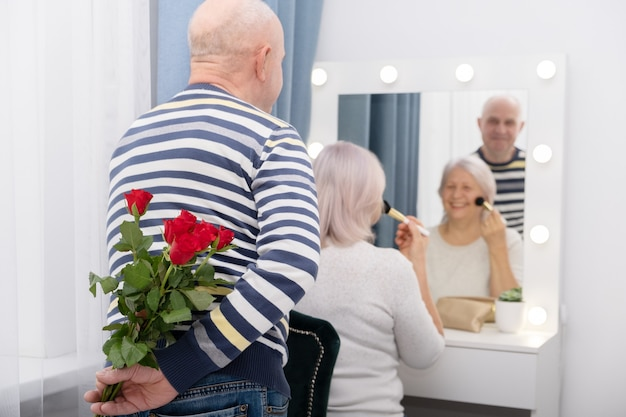 Senior man surprising wife with a rose. relationship, getting old together, love concept.