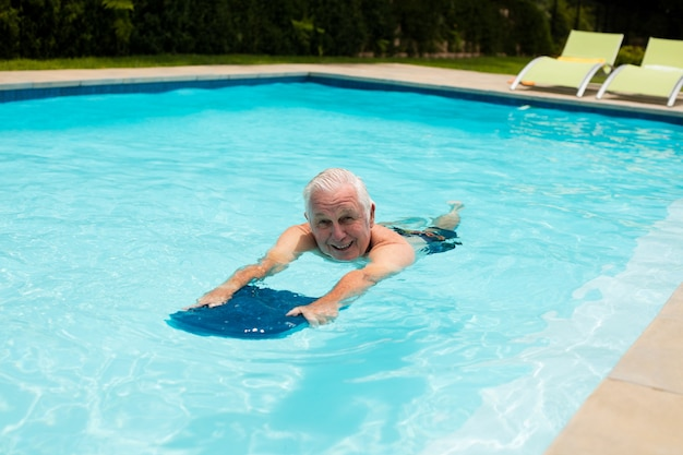 Старший мужчина плавает в бассейне в солнечный день