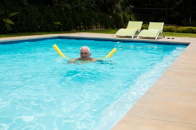 Старший мужчина плавание с надувной трубкой в бассейне
