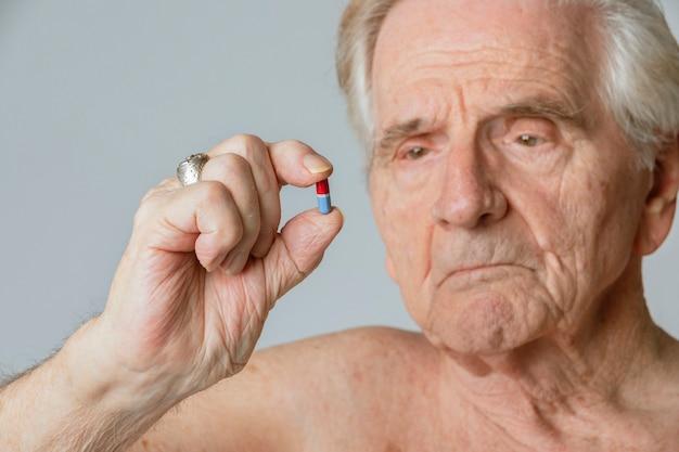 바이러스성 질병에 대한 캡슐 알약을 복용하는 노인