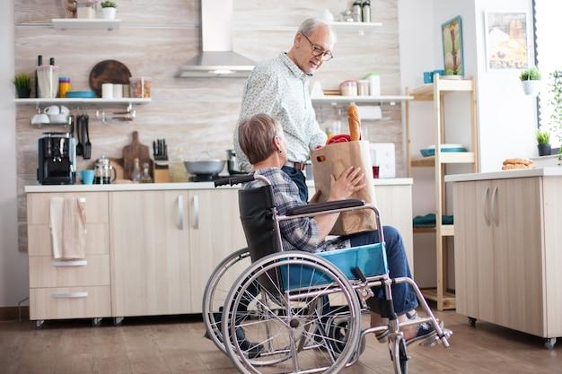 휠체어에 장애가 있는 아내에게서 식료품 종이 봉지를 가져가는 노인. 시장에서 신선한 야채와 함께 성숙한 사람들입니다. 보행 장애가 있는 장애인과 함께 생활
