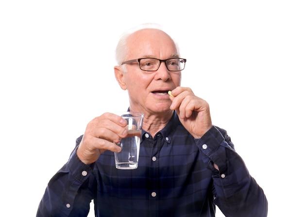 Старший мужчина принимает лекарство против белого