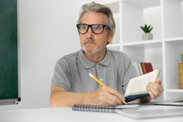 Senior man taking notes in class