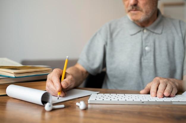 Uomo anziano che prende appunti in classe