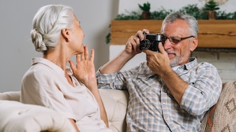 Senior man taking photo of her wife from camera