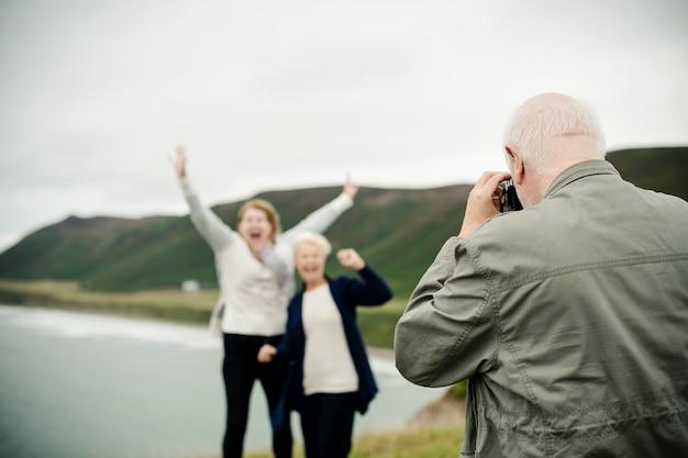Senior man taking a photo for senior women