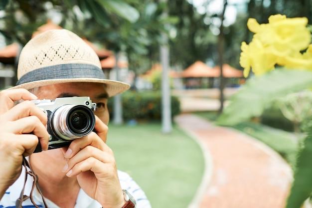 Старший мужчина фотографирует в парке