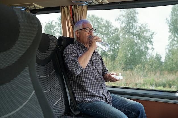 Старший мужчина принимает таблетку и пьет ее водой в автобусе