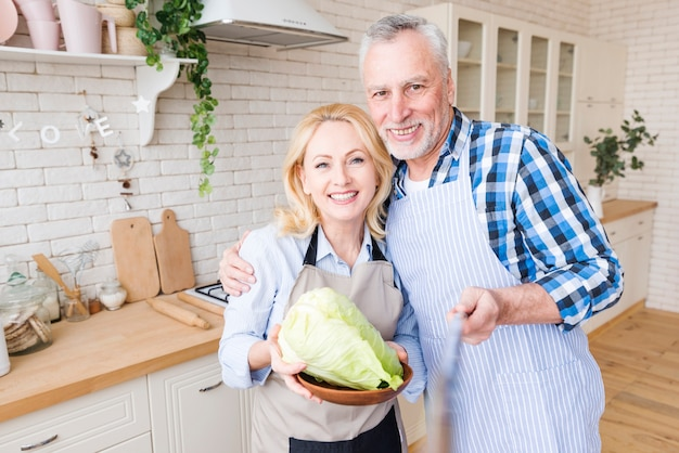 Senior man taking selfie with her wife holding cabbage in plate