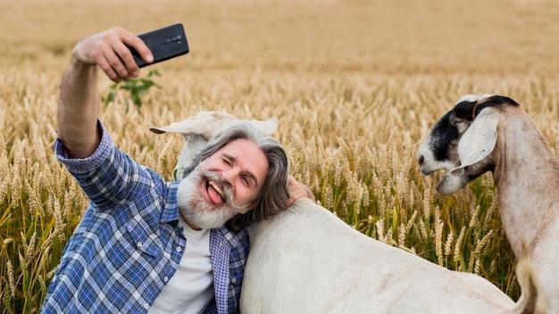Uomo maggiore che cattura slefie con capra