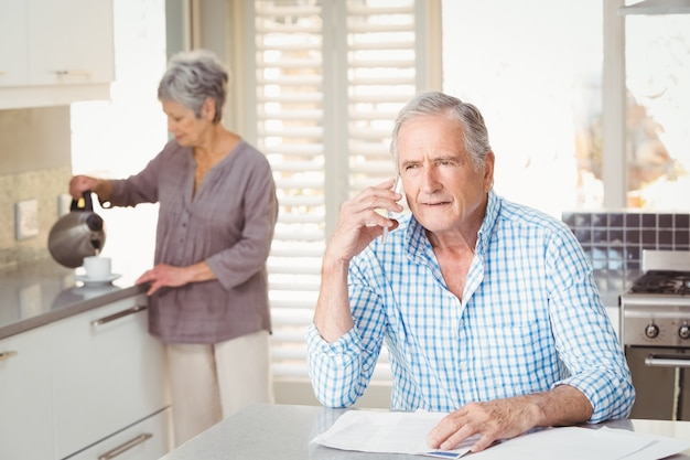 Senior man talking on mobile phone with wife making tea in background