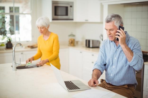 Старший мужчина разговаривает по мобильному телефону, а женщина моет тарелку на кухне