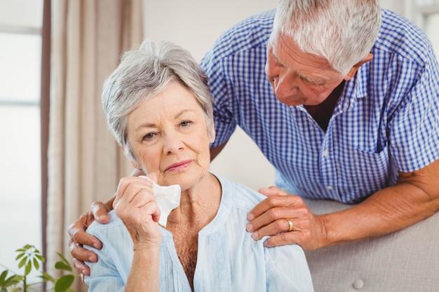 Senior man talking to upset senior woman in living room