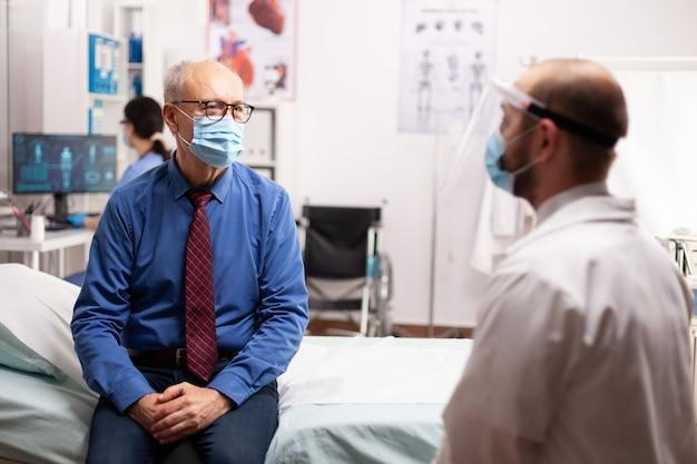 安全対策としてフェイスマスクを警告するベッドに座っている治療について医師と話している年配の男性世界的な健康危機、コロナウイルスパンデミック中の医療システム、プライベートclの病気の高齢患者
