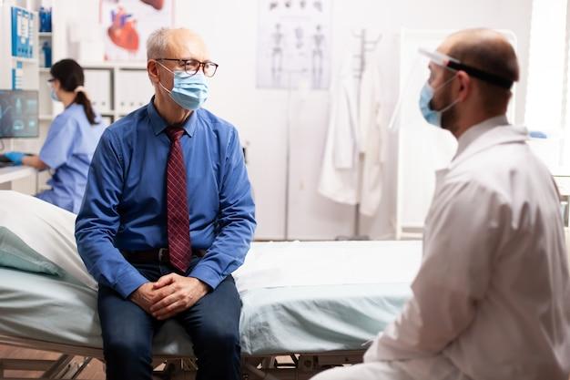 Covid19の過程で安全予防策としてフェイスマスクを警告するベッドに座っている治療について医師と話している年配の男性