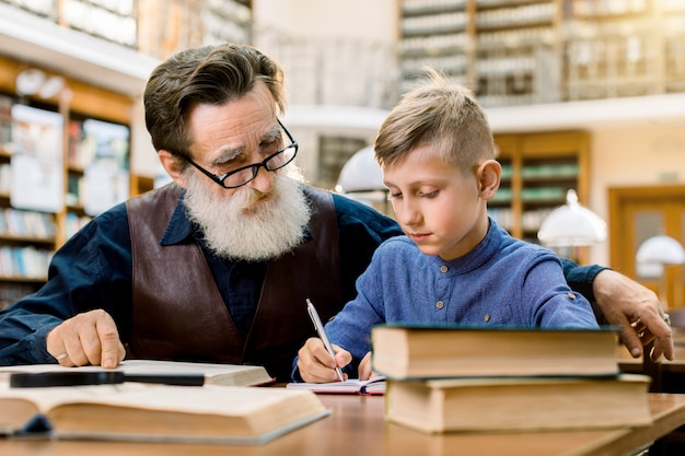 Senior man teacher or grandfather teaching little boy, his grandchild, reading book in library, while boy makes notes in his copy book. education, school concept
