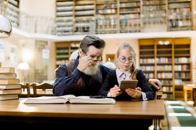 Senior man teacher with his little student girl is using a digital tablet, sitting together at the table in old ancient library.
