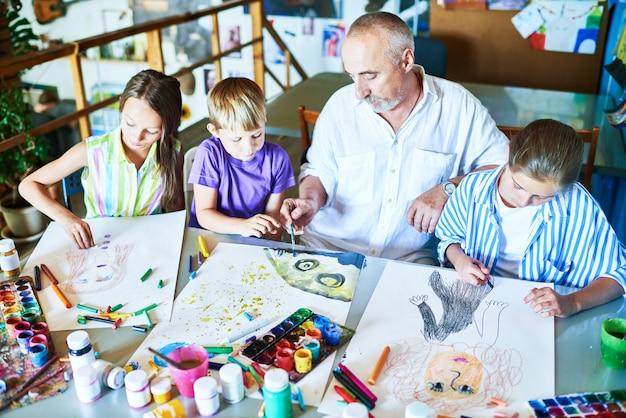 学校でアートクラスを教えるシニア男性