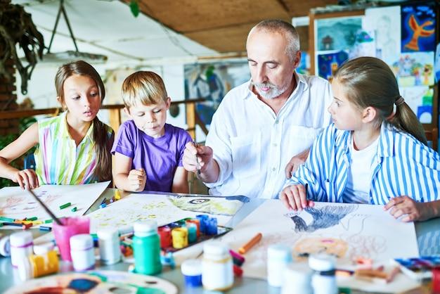アートクラスを教えるシニア男性