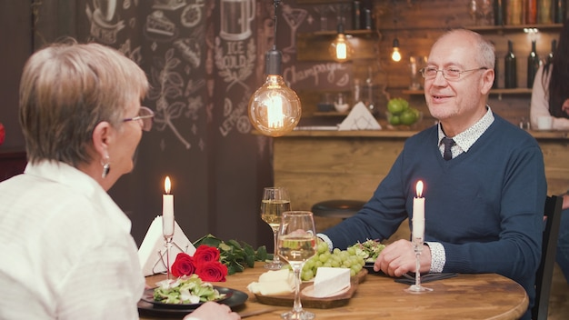Senior man telling an interesting story to his lovely old lady while having lunch. happy old couple. enjoying retirement.