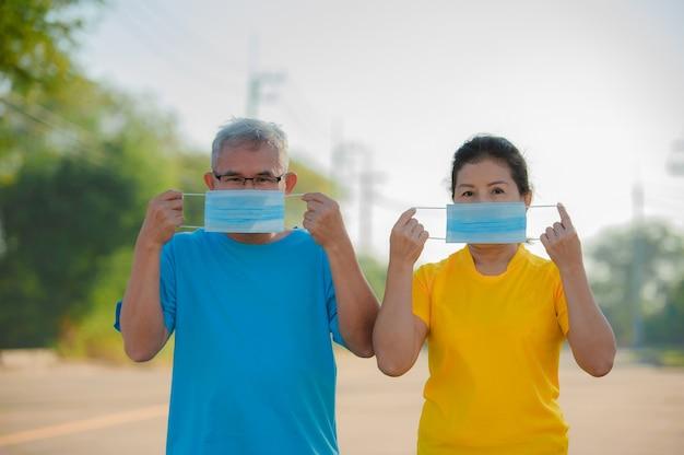 시니어 남자 후 시니어 여자는 코로나 바이러스를 보호하기 위해 얼굴 마스크를 착용합니다 .covid19