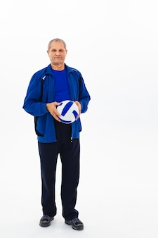 Senior man in a tracksuit holds the ball on white