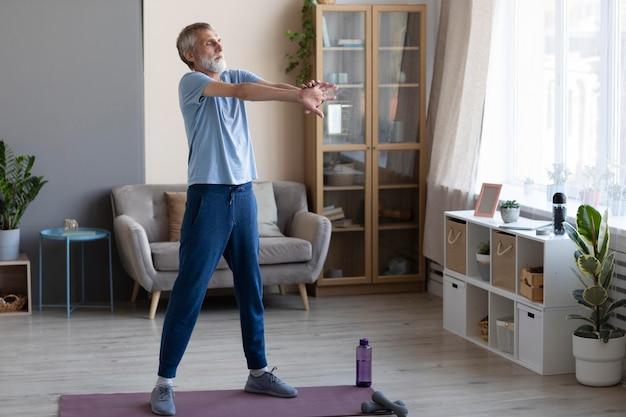 Старший мужчина тренируется дома