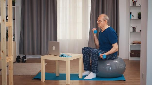 オンラインフィットネスレッスンを見ている上腕二頭筋を訓練する年配の男性。老人年金受給者が自宅でヘルスケアスポーツを健康的に訓練し、高齢者でフィットネス活動を行う