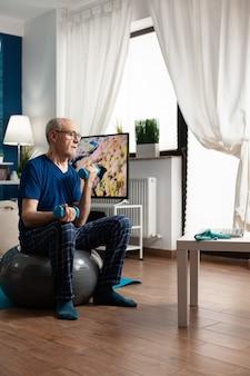 居間でスイスボールに座って腕の運動を行う体の抵抗を訓練する年配の男性