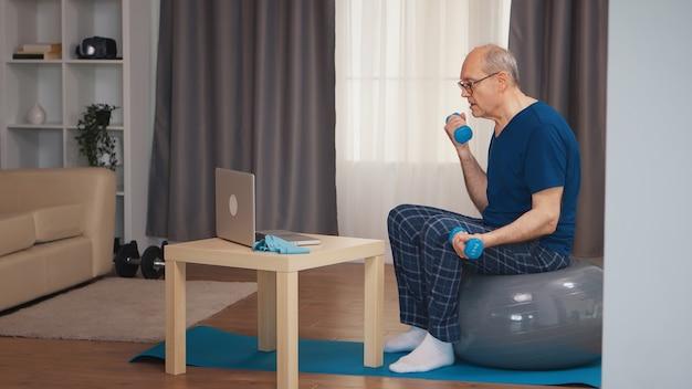 オンラインフィットネスプログラム中にダンベルでリビングルームでトレーニングする年配の男性。老人年金受給者が自宅でヘルスケアスポーツを健康的に訓練し、高齢者でフィットネス活動を行う