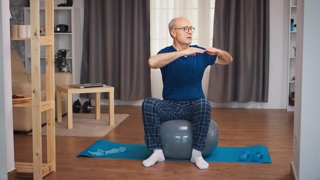 居間で安定ボールのトレーニングをしている年配の男性。老人年金受給者が自宅でヘルスケアスポーツを健康的に訓練し、高齢者でフィットネス活動を行う