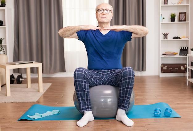 居間で安定ボールのトレーニングをしている年配の男性