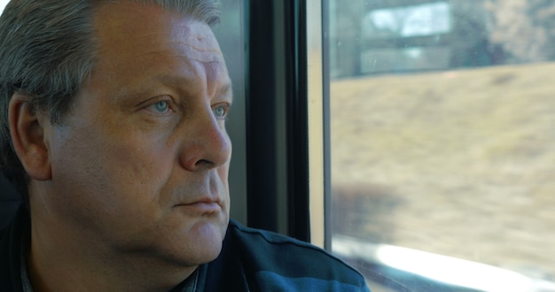 電車で旅行する年配の男性