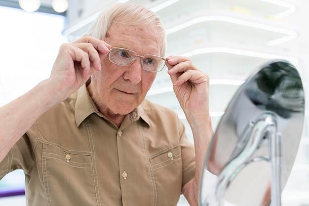 Uomo anziano che prova un nuovo paio di occhiali