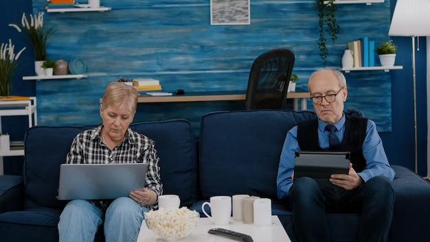 아내가 노트북을 사용하는 동안 태블릿을 사용하는 노인